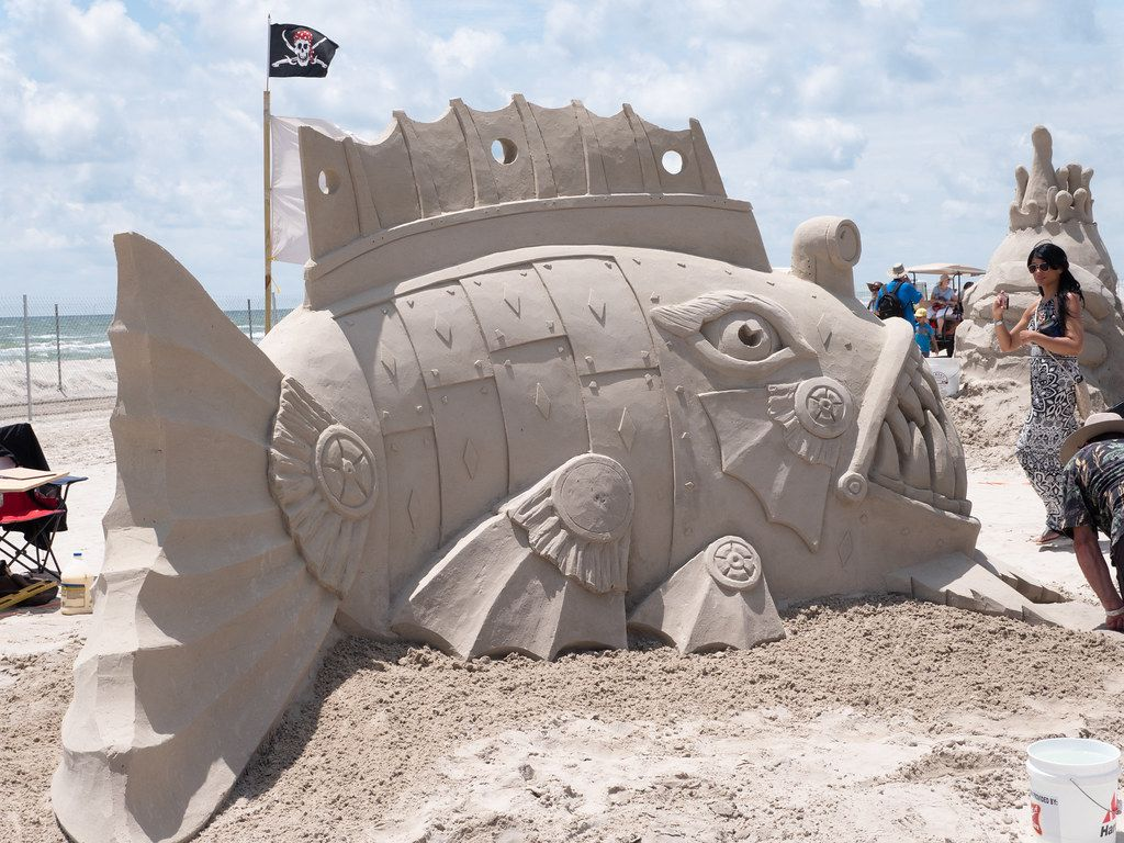 Woman looking at a giant fish made from sand at the Port Aransas sandfest